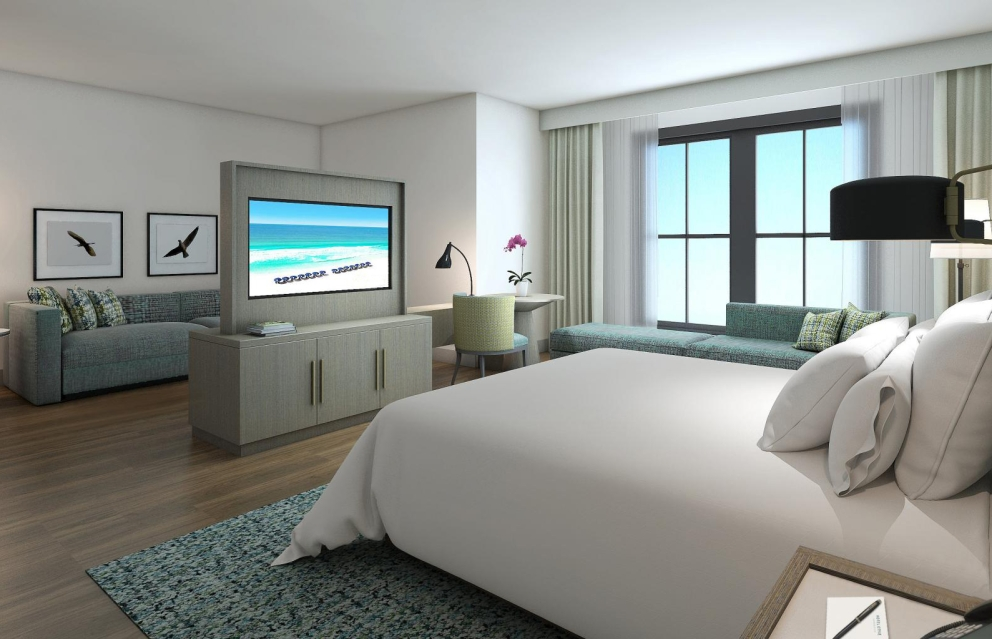 A King Suite at Hotel Effie with a large TV at the foot of the bed and big windows letting in lots of natural light.