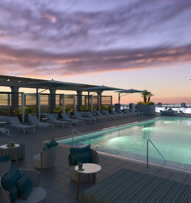 The rooftop pool and lounge at nighttime with a beautiful sunset.