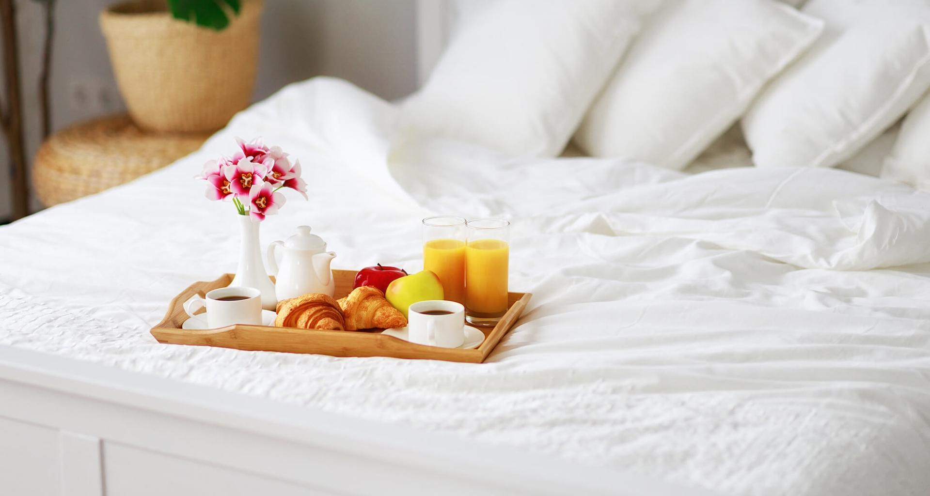 A fresh breakfast on a tray on a bed with white linens.