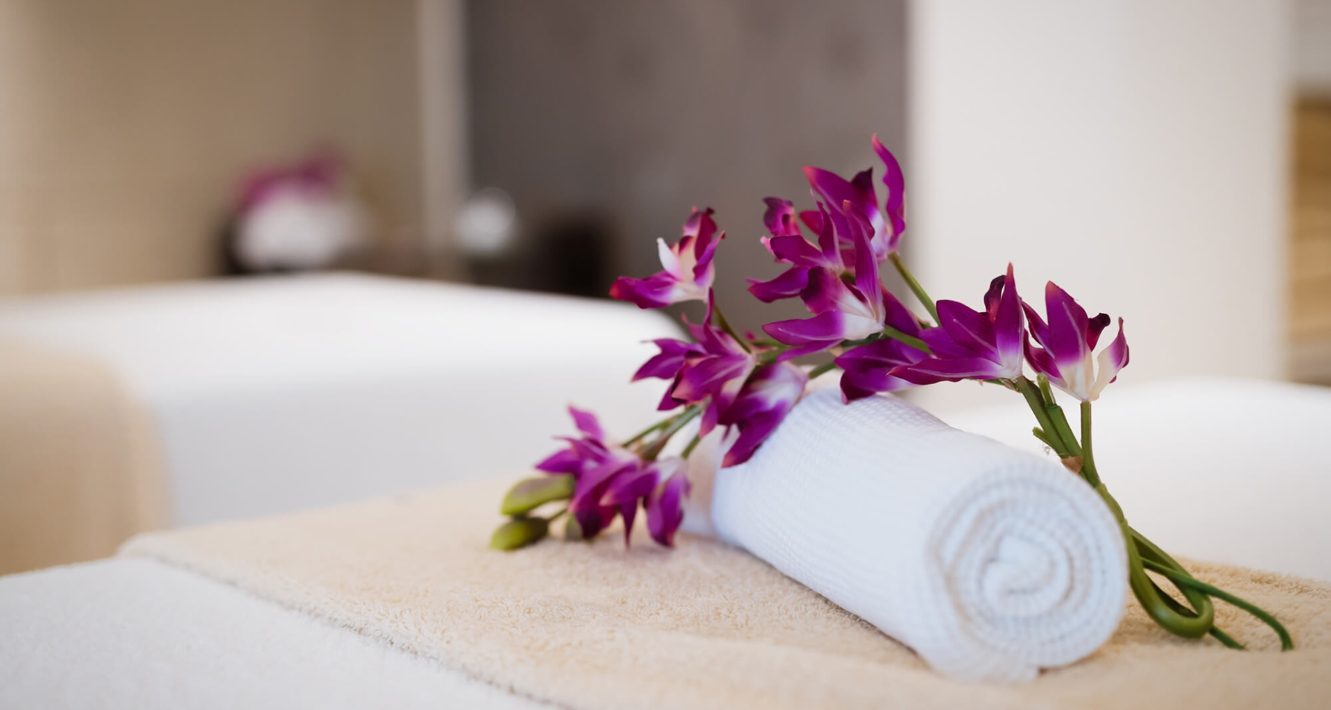 A white towel rolled up and placed on a bed with a flower laying beside it