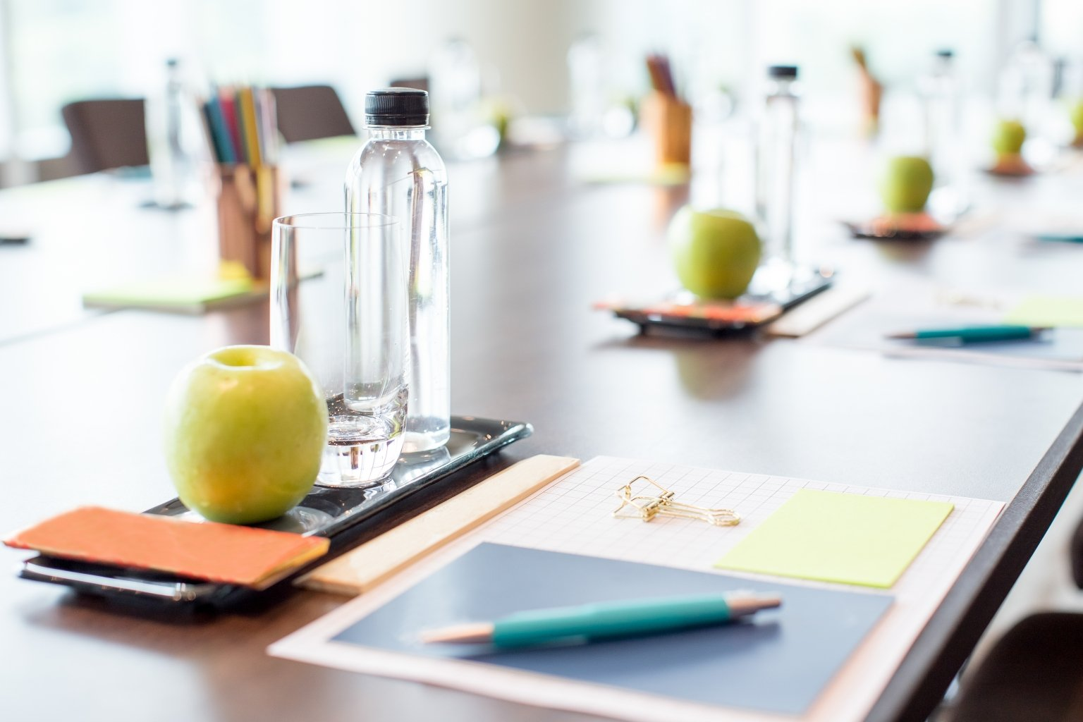 A table set for a business meeting with a pen, pad of paper, apple, and bottle of water