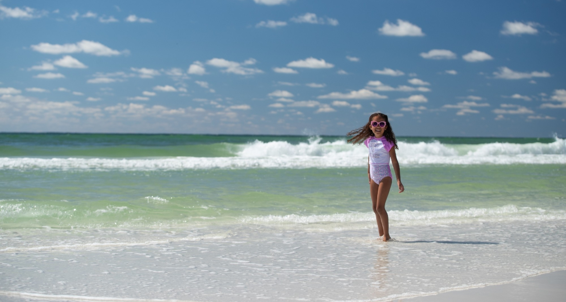 A young girl walks on a white sand beach at Hotel Effie