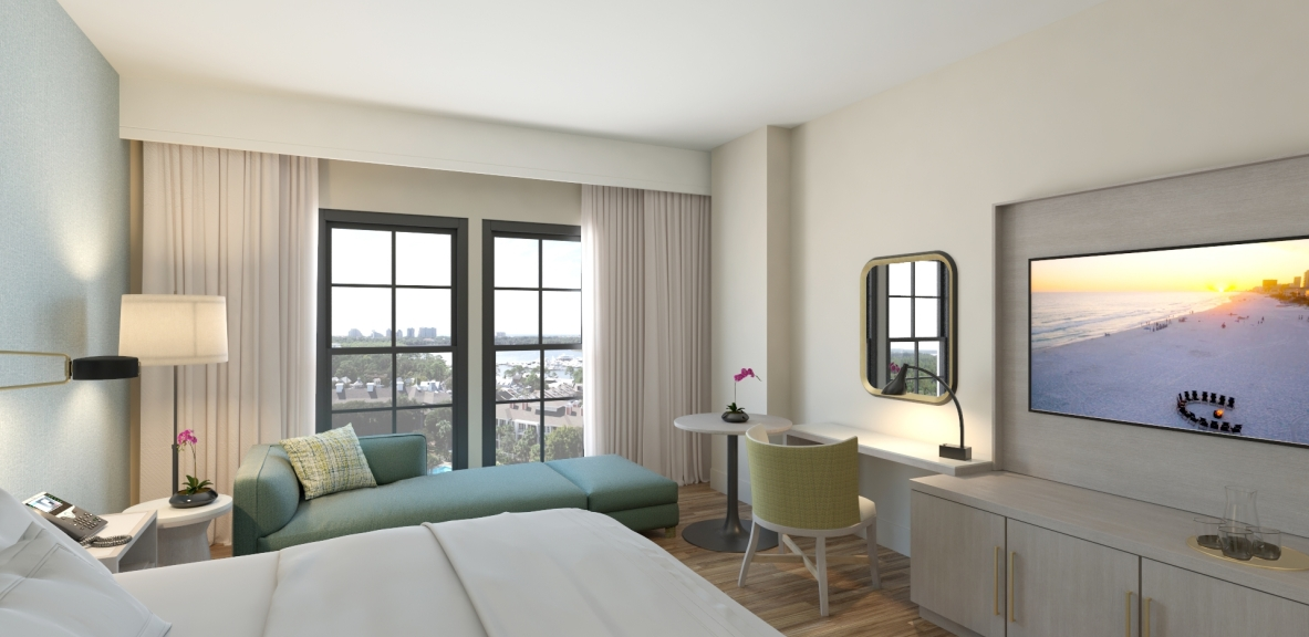 A suite a Hotel Effie with a bed, a desk and chair, and a chaise lounge by a window overlooking a view of the water.