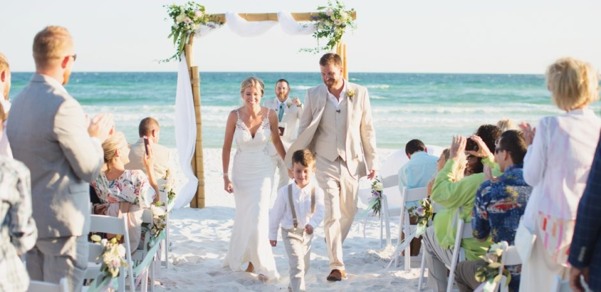 Callie and Roy walking down the isle on a beach