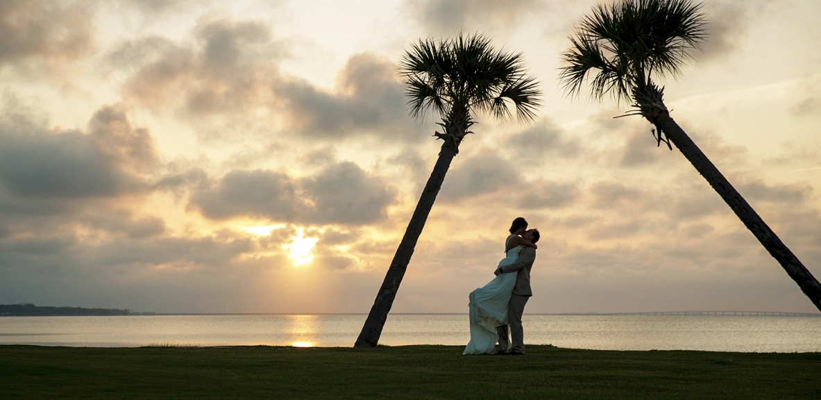A newly wed couple kissing on the beach with palm trees