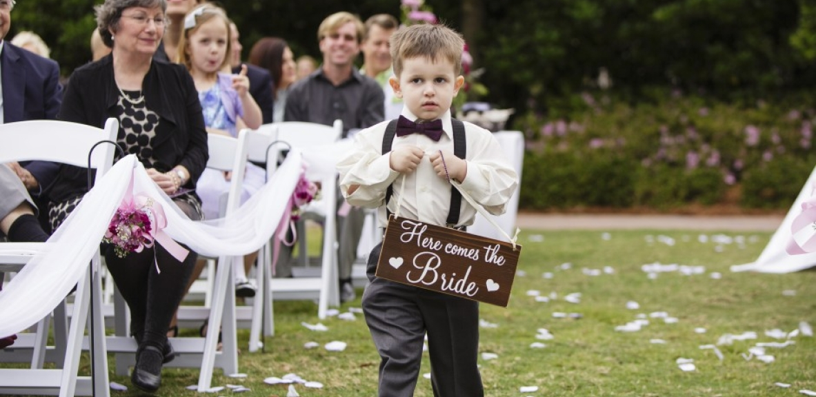 The young ring bearer walking down the isle