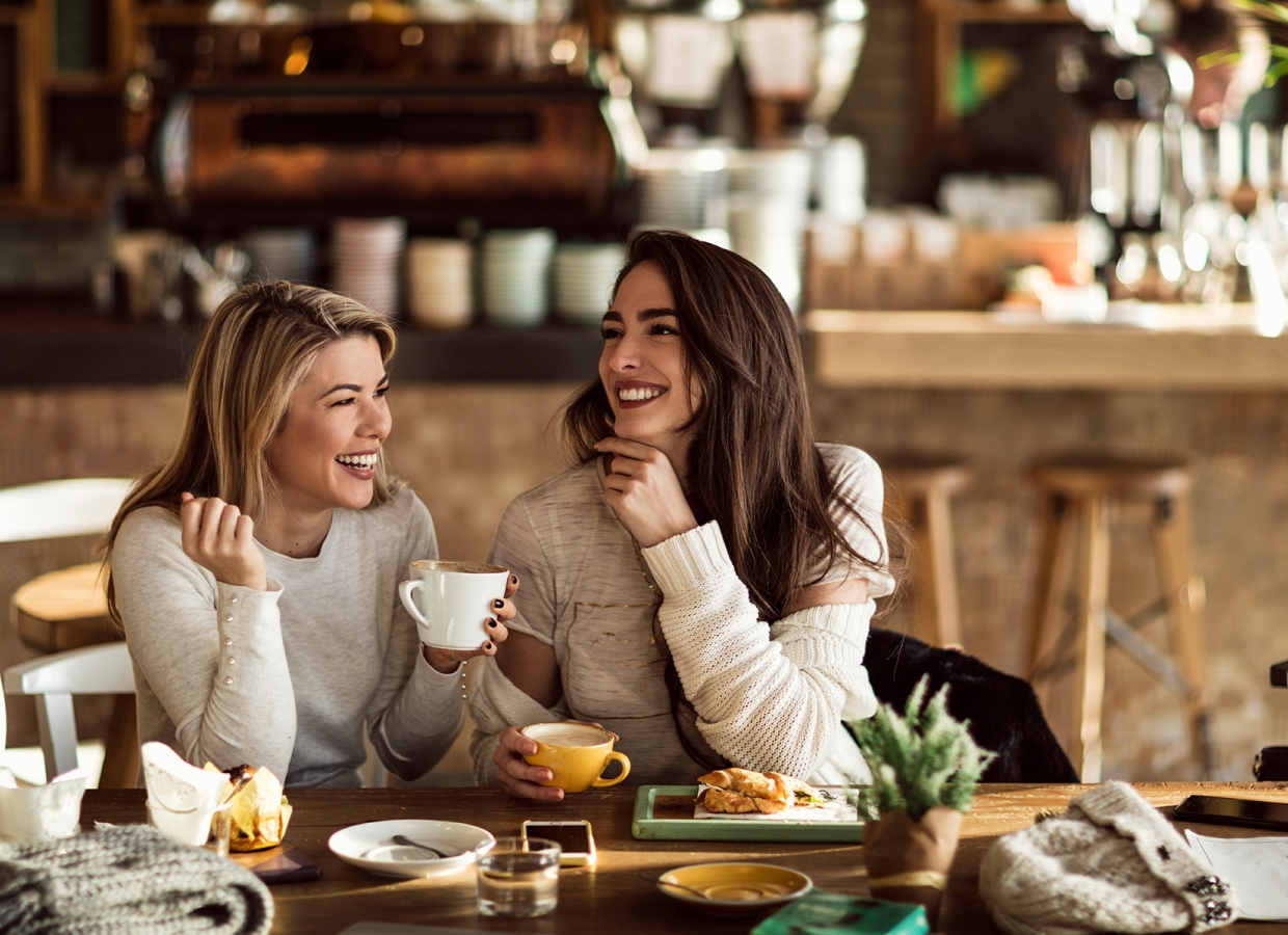 two women laughing over coffee