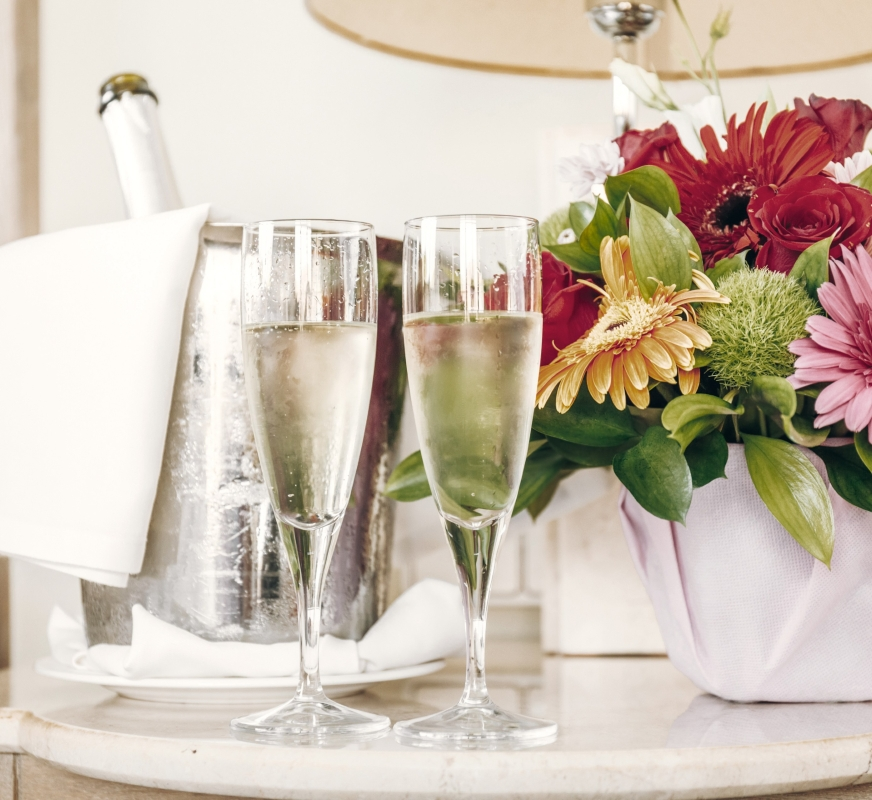 two champagne glasses and flowers on a nightstand.